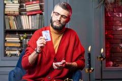 Adivino barbudo maduro que tiene cierta inspiración que trabaja en casa imagen de archivo libre de regalías