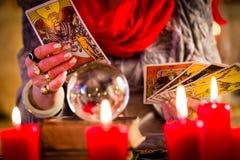 Adivino durante la sesión con las cartas de tarot Foto de archivo