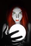 Adivino magnífico del pelirrojo que sostiene la bola de cristal la mujer hermosa intenta mirar en el futuro Foto de archivo