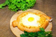 Adjara-khachapuri Brot auf einem Brett mit Käse Stockfoto