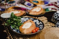 Adjara khachapuri on the eastern table. egg in hot bread on oriental plates is in a restaurant stock image