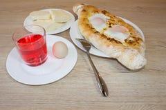 Adjarian-khachapuri auf a auf einer Platte Öffnen Sie Torte mit Käse in Form des Bootes Stockfotos