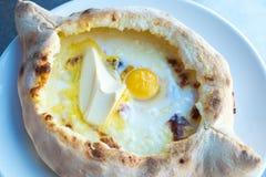Adjarian-khachapuri mit Eiern und Butter auf dem Tisch Stockfotos