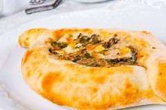 Adjarian-khachapuri mit Käse und Spinat Lizenzfreie Stockfotografie