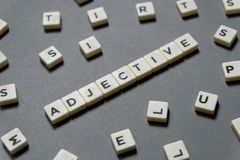 Adjective word made of square letter word on grey background. stock image