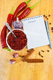 Adjika with fresh peppers. Tabasco in a white cup, fresh red peppers, garlic, cloves, cinnamon, pea black pepper, a notepad with the word recipe and a silver pen Royalty Free Stock Images
