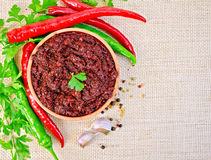 Adjika with hot pepper and parsley on burlap Stock Photo