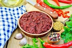 Adjika mit frischen Peperoni und Öl an Bord Lizenzfreies Stockfoto