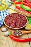 Adjika mit Peperoni und Öl an Bord Lizenzfreies Stockfoto