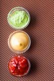 Adjika, mostarda, wasabi em um close-up da bacia de vidro Imagem de Stock