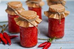 Adjika, salsa al pomodoro rossa con pepe immagini stock