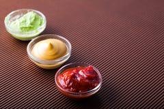 Adjika, Senf, Wasabi in einer Glasschüssel Stockbilder