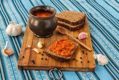 Adjika slathered хлебом на разделочной доске стоковые фото