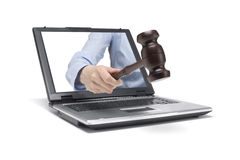 Adjudgement. A hand reaches out of a laptop with a wooden hammer Stock Image