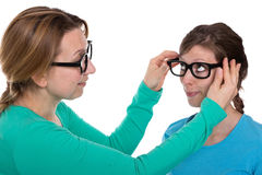 Adjust glasses. Woman lets another women test some glasses Royalty Free Stock Photography