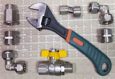 Adjust wrench power grip and elements of water and gas shutoff valves, flat lay.  Stock Image