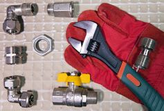 Adjust wrench power grip and elements of water and gas shutoff valves on a working protective glove, flat lay.  Stock Image