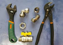 Adjust wrench power grip, groove joint pillers and elements of water and gas shutoff valves, flat lay Stock Photo