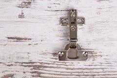 Adjustable hinge on grunge wooden background Royalty Free Stock Image