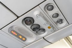 Adjustable ights and air conditioners overhead seat controls of a commercial aircraft in an airplane with no-smoking and seat belt Royalty Free Stock Image