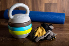 Adjustable kettlebell, cycle gloves dumbbells and yoga mat on wooden background. Weights for a fitness training. Royalty Free Stock Image