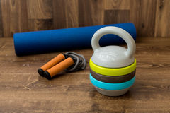 Adjustable kettlebell, jumping rope and mat for fitnes on wooden background. Weights for a fitness training. Stock Image
