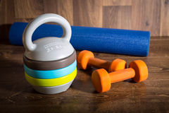 Adjustable kettlebell, pair of orange dumbbells and yoga mat on wooden background. Weights for a fitness training. Stock Photography
