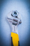 Adjustable key and stainless screw nut on metallic Royalty Free Stock Image