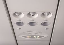 Overhead seat controls. Adjustable lights and air conditioners overhead seat controls of a commercial aircraft in an airplane with no-smoking and seat belt on Stock Photography
