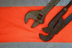 Adjustable and pipe wrenches against the background of an orange signal worker shirt. Still life associated with repair, railway. Or plumbing works Stock Photo