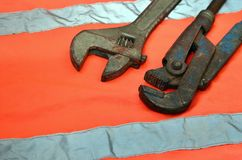 Adjustable and pipe wrenches against the background of an orange signal worker shirt. Still life associated with repair, railway. Or plumbing works Stock Photos