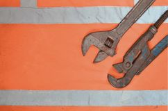 Adjustable and pipe wrenches against the background of an orange signal worker shirt. Still life associated with repair, railway. Or plumbing works Stock Photography