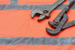 Adjustable and pipe wrenches against the background of an orange signal worker shirt. Still life associated with repair, railway. Or plumbing works Royalty Free Stock Image