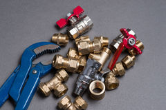 Adjustable spanner with assorted plumbing fittings on grey Royalty Free Stock Image