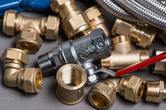 Adjustable spanner with assorted plumbing fittings and hose on grey Stock Photo