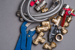 Adjustable spanner with assorted plumbing fittings and hose on grey Royalty Free Stock Photo