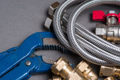 Adjustable spanner with assorted plumbing fittings and hose on grey Royalty Free Stock Photography