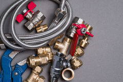 Adjustable spanner with assorted plumbing fittings and hose on grey Stock Image