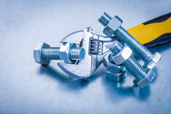 Adjustable spanner bolt details and screw nuts on. Metallic background construction concept Stock Images