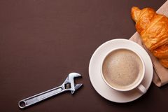 Adjustable spanner and cup of coffee with croissant on brown table. Adjustable spanner and cup of coffee with croissant on a brown table stock photography