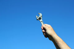 Adjustable spanner held up with a blue sky Stock Images