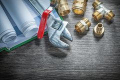 Adjustable spanner plumbing pipe connectors rolled construction. Plans water valve notebook pen Stock Images