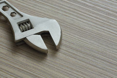 Adjustable wrench closeup on wooden background. Extreme close up Royalty Free Stock Photos