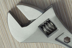 Adjustable wrench closeup on wooden background. Extreme close up Stock Photography