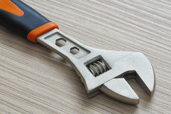Adjustable wrench closeup on wooden background. Extreme close up Stock Image
