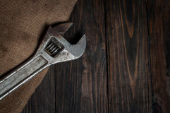 Adjustable wrench on dark wooden background. Royalty Free Stock Image