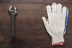 Adjustable wrench and gloves. On the wooden background Stock Photos