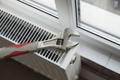 Adjustable wrench on the heating radiator