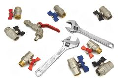 Adjustable Wrench And Many  Ball Valves  On White, Close Royalty Free Stock Photos