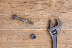 Adjustable Wrench and nut on wooden background Stock Image